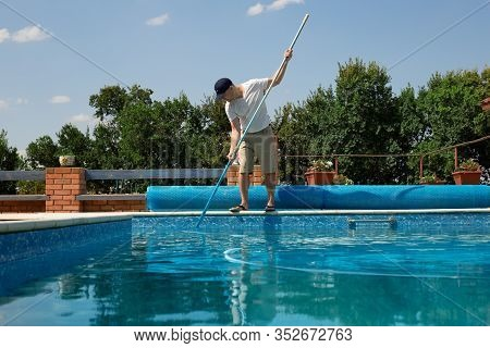 Cleaner Of The Swimming Pool. Man Cleaning Outdoor Swimming Pool With Vacuum Tube Cleaner In Summer.