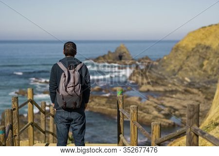 Man With A Backpack Seeing Praia Dos Machados Beach In Costa Vicentina, Portugal
