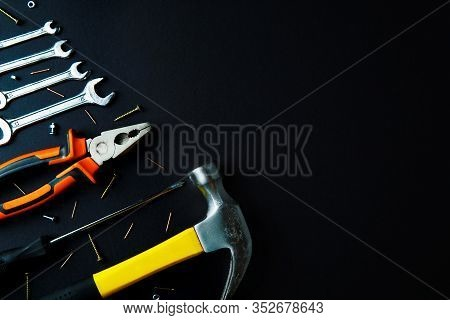 Construction Tools For Home Renovation On Black Background. Hammer, Hand Saw, Pliers, Screwdriver, W