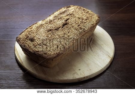 Freshly Baked Buckwheat Bread. A Loaf Of Bread Lies On A Round Kitchen Board On A Brown Wooden Table