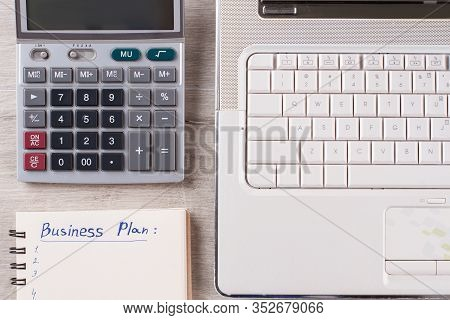 Laptop, Calculator, Notepad On Table. Typical Office Clerk Flatlay. Flatlay On Wooden Background Clo
