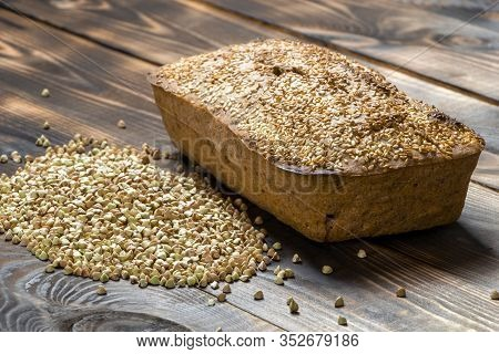 Useful Buckwheat Bread With A Golden Crust And A Bunch Of Green Grains Nearby On A Wooden Table. Veg