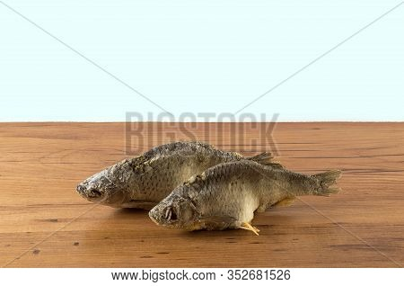 Dried Fish On The Table. Salty Dry River Fish On A White Background. Dead Dry Salty Fish - Snack To