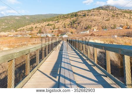 Looking Across Wooden Trestle Bridge On Kettle Valley Rail Trail To View Of Vineyards And Mountains