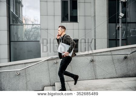 Hurry Up! A Young Man Is Late For A Very Important Meeting, He Runs Up The Stairs With A Laptop In H