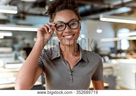 Close Up Portrait Of Cheerful Young Businesswoman In Casual Wear And Glasses Smiling At Camera While