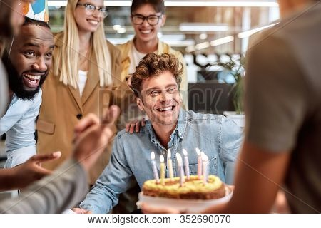Best Wishes. Young Happy Man Blowing Candles On Cake While Celebrating Birthday Among Smiling Mixed