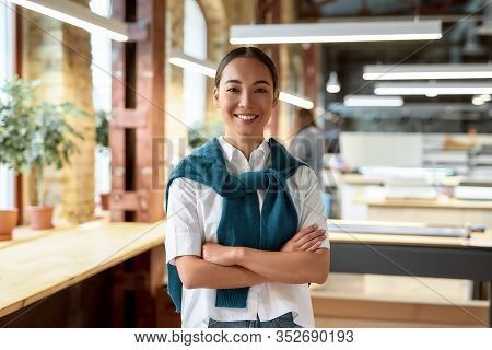 Portrait Of Attractive Ambitious Asian Businesswoman In Casual Wear Smiling, While Looking At Camera