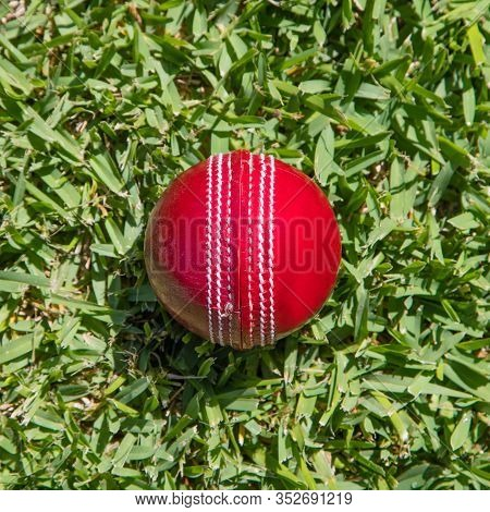 Closeup Of Red Leather Cricket Ball On Green Grass. Cricket Is A Popular Sport In Nations Such As Au