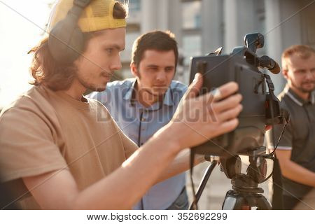 Close Up Portrait Of Young Professional Cameraman In Headphones, Recording A Video Footage Using A P