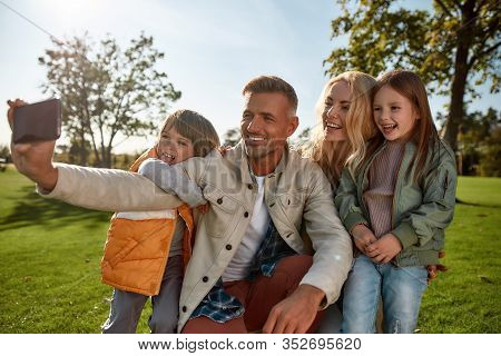Portrait Of Cheerful Parents With Children Taking Pictures Using Smartphone In The Park On A Sunny D