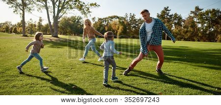 Full-length Portrait Of Happy Mother, Father, Little Boy And Girl Running And Playing Catch Game In
