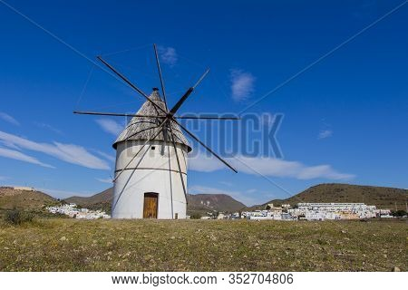 Traditional Windmill And Behind The Village Of El Pozo De Los Frailes, Windmill Traditional In Spain