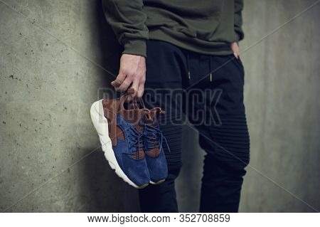 Young Man Holding Blue Nike Air Huarache Sport Shoes Shot On Grey Background. Nike Sneakers, Trainer