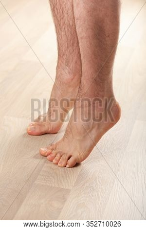 man doing flatfoot correction gymnastic exercise standing on toes at home