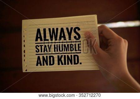 Inspirational Quote - Always Stay Humble And Kind. With A Paper Note In Young Woman Hand On Light Br