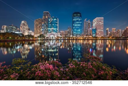 Lake With Purple Flowers In City Park Under Skyscrapers At Night. Benjakiti Park In Bangkok, Thailan