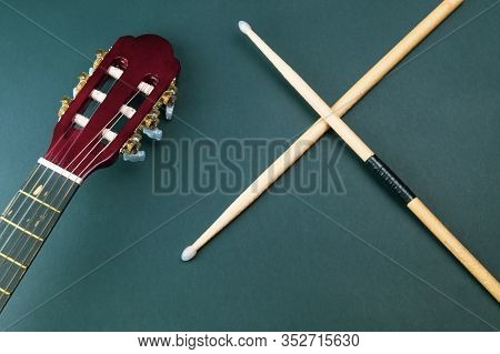 Drumsticks And Guitar Headstock Close Up. Acoustic Musical Instrument