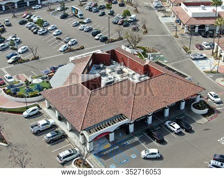Aerial View Of Typical Small Town Shopping Center With Supermarket, Bank, Restaurant And Parking For