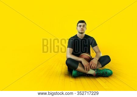 Young sportsman basketballer sitting on yellow background