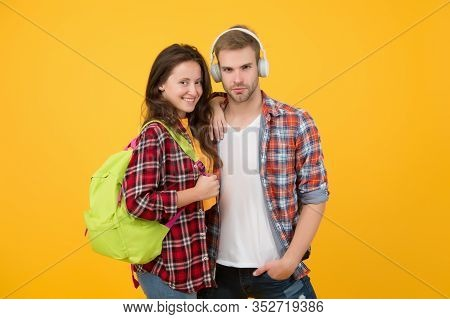 Portrait Of Attractive Young Students Couple. Cheerful Woman Wearing Backpack. Guy In Headphones. On