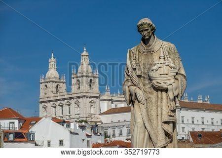 LISBON, PORTUGAL - CIRCA FEB 2019: Sculpture of Sao Vicente St. Vincent of Saragossa, with Igreja de Sao Vicente de Fora in the background