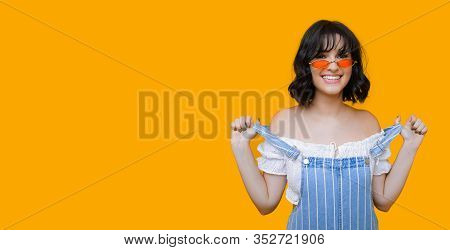 Smiling Caucasian Girl With Black Curly Hair And Eyewear Is Pulling Her Rompers On A Yellow Backgrou