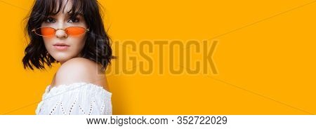 Caucasian Girl With Beautiful Black Hair Is Looking Through Her Sunglasses While Standing On A Yello