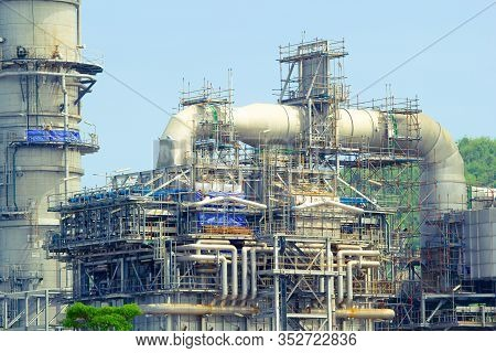 Oil Refinery Plant And Refinery Tank With Blue Sky Background.