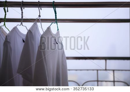 White T Shirts Hung On Cloth Hangers On Cloth Line At The Balcony Of Residential Building In A Rainy