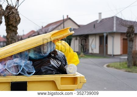 Overfilled Trash Dumpster  Full With Mixed Trash On A Street