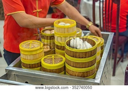Waitress In Chinese Costume Serving Dimsum In Bamboo Steamer Boxes