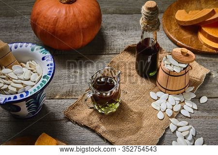 Cold Pressed Pumpkin Seed Oil In A Glass Bottle And Gravy Boat, Raw Pampkin Decorated With Seeds In