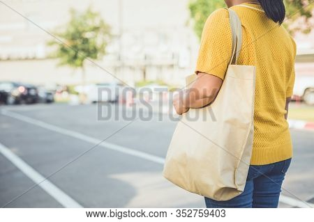 Woman Using Cotton Bag In Shopping Center To Replace Plastic Bag Usage