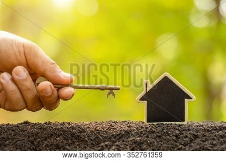 Wooden House Growing In Soil And Vintage Key On Green Nature Blur Background. Key To Success About H