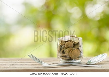 Coins In Clear Money Jar, Fork And Spoon On Wooden Table With Green Blur Light Background. Savings M
