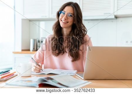 Image of a positive cheerful beautiful young woman sit indoors at home using laptop computer writing notes in notebook studying.