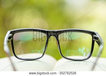 Book And Eye Glasses On Wooden Table With Abstract Green Nature Blur Background. Reading And Educati