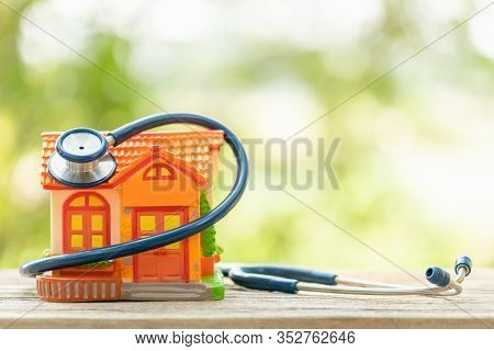 Hand Holding Blue Stethoscope And Orange House Model On Wooden Table. Home And Building Checking