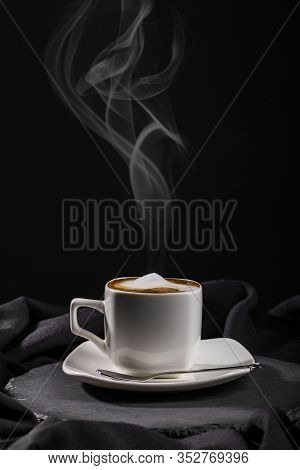 Steaming Cup Of Coffee With Milk Froth On White Saucer And Board Over Dark Fabric Folds Background