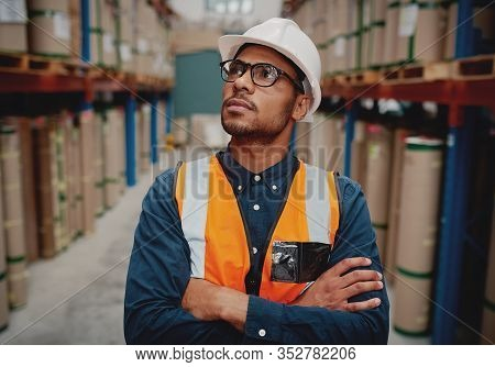 Portrait Of Serious Supervisor In Warehouse Standing With Folded Hands Looking High At Shelves With