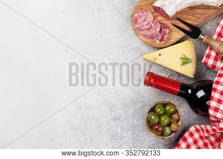 Italian cuisine food. Cheese, salami, olives and wine. Top view flat lay on stone table with copy space