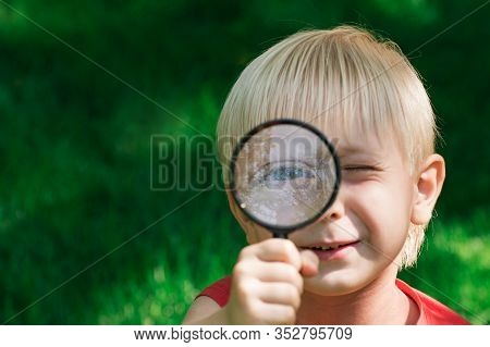 Cute Curious Child Looking Through A Magnifying Glass. Serious Boy Exploring The Environment