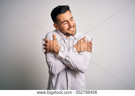 Young handsome man wearing elegant shirt standing over isolated white background Hugging oneself happy and positive, smiling confident. Self love and self care