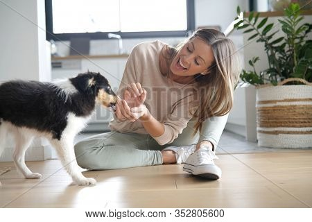 Woman at home sittign on floor with puppy dog