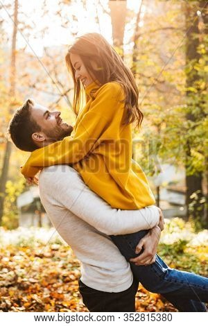 Beautiful young happy couple in love embracing while spending time in the autumn park