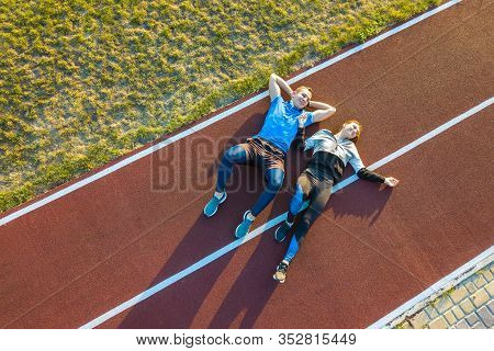 Top Down Aerial View Of Two Young People Sportsman And Sportswoman Laying On Red Rubber Running Trac