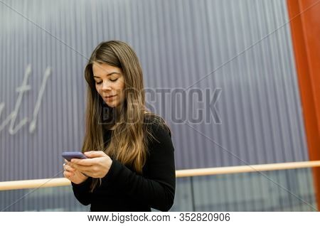 Lifestyle portrait of Real Young pretty woman with cell-phone