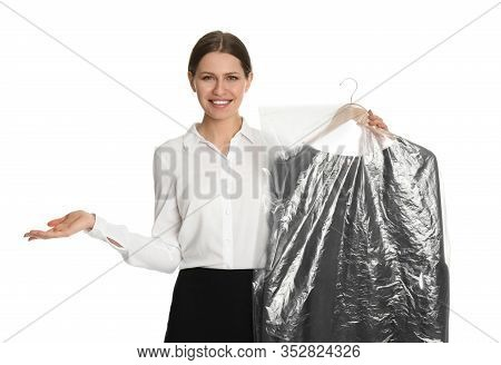 Young Woman Holding Hanger With Dress In Plastic Bag On White Background. Dry-cleaning Service