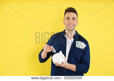 Happy Man Putting Money Into Piggybank On Yellow Background. Space For Text